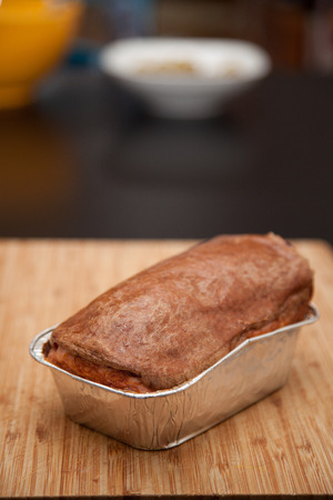 meat loaf: Leberkaese a bavarian pork meat loaf in aluminum dish on wood cutting board. Stock Photo