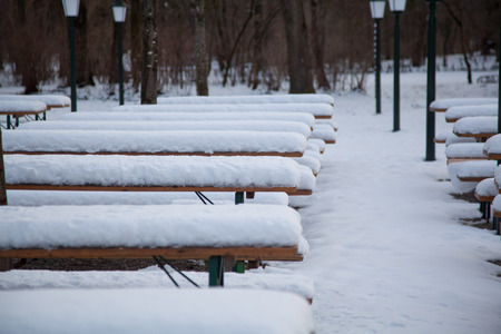 snow break: beergarden in munich in winter. table covered with snow.
