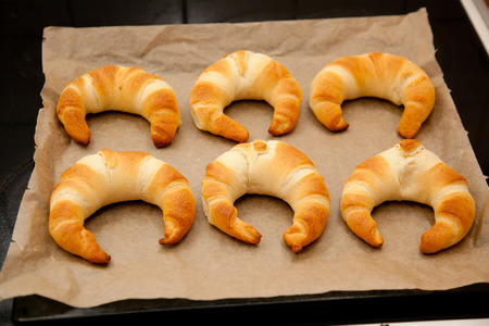 baking tray: croissants on a baking tray with baking paper. Stock Photo
