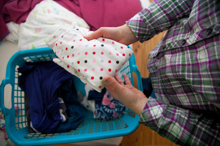 laundry room: woman doing the laundry in the sleeping room. she wears a plaid shirt. she puts a dotted shirt in a basket.