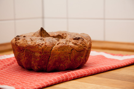 worktop: selfbaked bread in guglhupf shape on red kitchen towel, napkin, or table cloth. on a oak wood kitchen worktop. Stock Photo