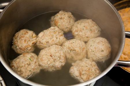 boiling pot: Dumplings in a boiling pot. 9 dumplings cooking in a boiling pot. dough made of bread crumbs.