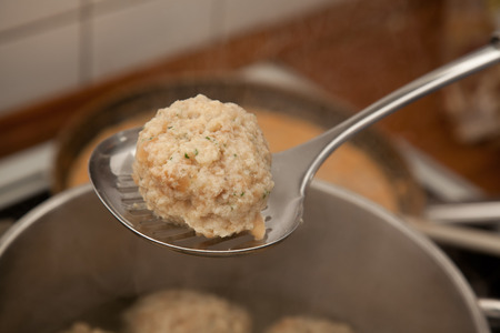 boiling pot: dumpling on a skimmer in a kitchen in front of a boiling pot. dumpling made of bread and roll crumbs