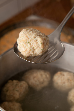 skimmer: dumpling on a skimmer in a kitchen in front of a boiling pot. dumpling made of bread and roll crumbs