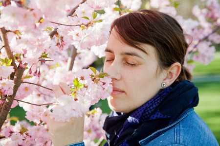eyes shut: woman smelling at almond tree. She has her eyes shut. She has no hay fever.