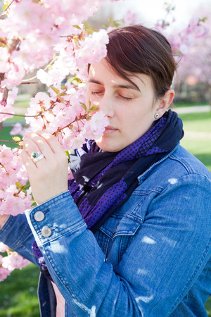 antihistamine: woman smelling at almond tree. She has her eyes shut. She has no hay fever.
