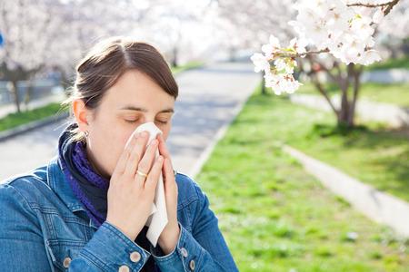 여자 재채기. 화분증 꽃가루 때문에. 벚꽃이 피었다. 그녀는 손수건을 가지고 코를 불었습니다.