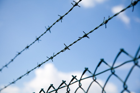 oppression: barbed wire fence with sky and cloud background.