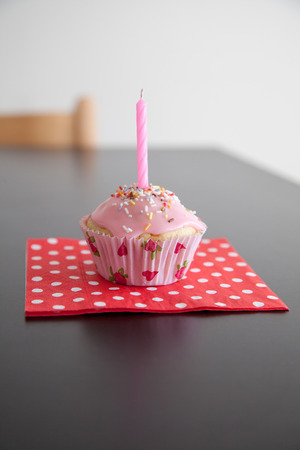 Pink Muffin on a dotted napkin with a birthday candle. On the streusel muffin are and icing. The Muffin stands on a black table. photo