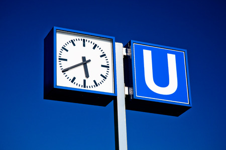 u bahn: u bahn subway sign and clock at a train station at a sunny with blue sky.