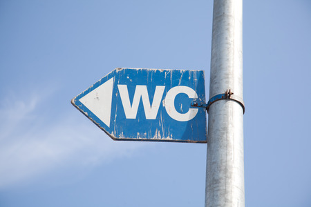 wiesn: wc sign in blue color. pointing in direction of the toilets at oktoberfest in munich.