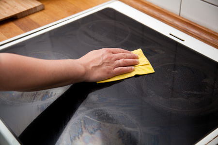 hob: woman wipes ceramic hob with a yellow wipe in a kitchen.