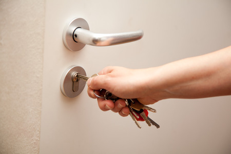appartment: woman turns key in door lock in flat, house or appartment,