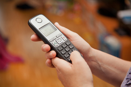 telephone: woman typing number into phone at home