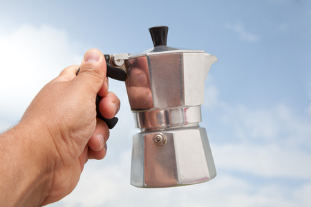 percolator: man holding percolator in his hand in front of blue sky.