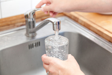 vrouw met een glas op waterkraan en het vullen van water.