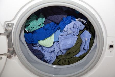 lavanderia: ropa mojada azul en la lavadora con la tapa abierta.