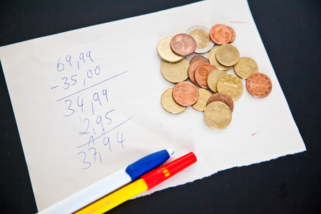 household money: note with calculation. on the note are euro cent coins and a pen Stock Photo