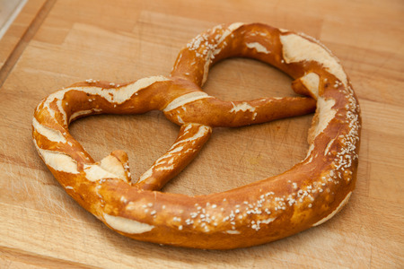 pretzel: giant pretzel on cutting board.
