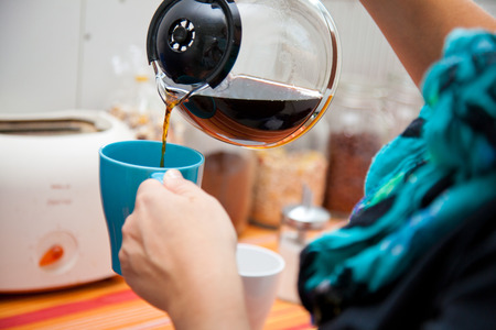 woman pouring coffee pot into a coffee mug in the kitchen. Stock Photo