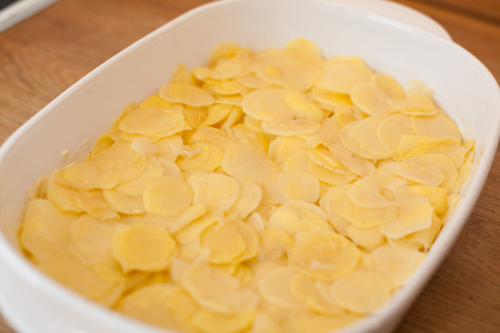 casserole dish: potato gratin in casserole dish in the kitchen on wooden tabletop. Stock Photo