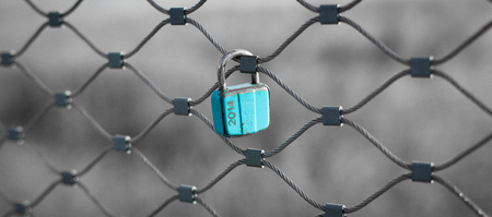 chainlink: love security lock in blue color on chainlink bridge. Stock Photo