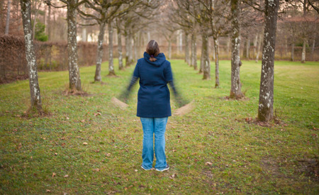 happieness: woman standing in a park in fall and raises her hands into the air with motion blur. Stock Photo