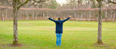 happieness: woman standing in a park in fall and raises her hands into the air