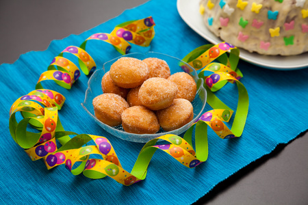 chocolate birthday cake: filled donuts, called krapfen or berliner. There are also colorful streamer on the table. Stock Photo