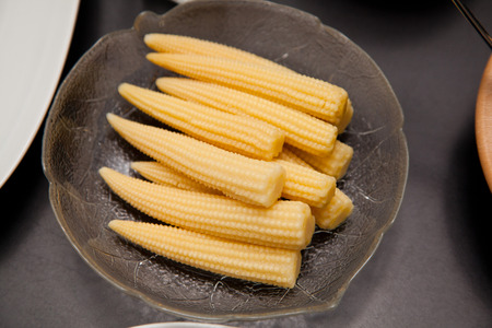 fingerfood: mini corn ears on a glass plate at a party. Stock Photo