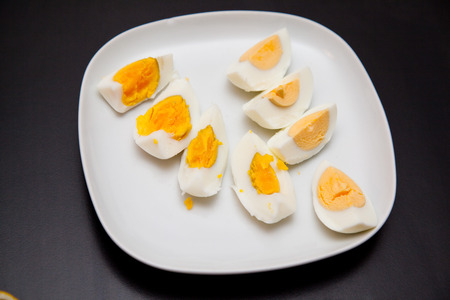 hard boiled: hard boiled eggs on a white plate on a black table.