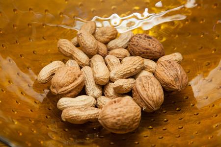 glass bowl: Peanuts and walnuts in a glass bowl.