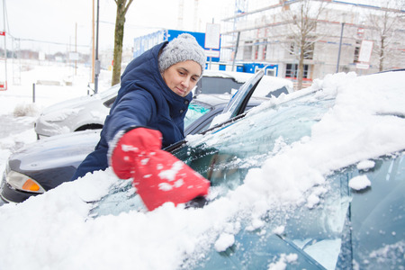 scraper: Woman is removing snow from car window with ice scraper in winter. Stock Photo