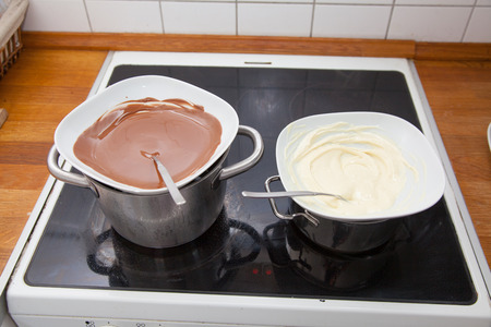 molted: Black and white chocolate couverture in water bath in the kitchen on the stove.