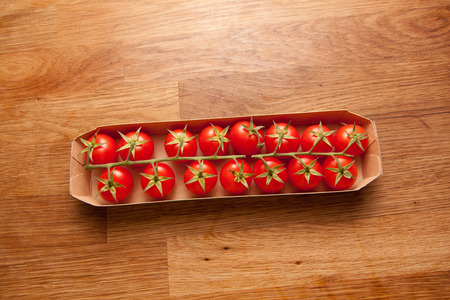 Cluster tomatoes on oak kitchentop in the kitchen in a cardboard box.