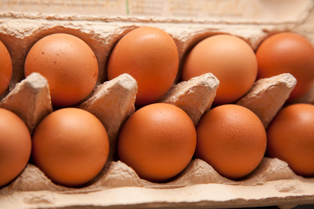 food staple: Box with brown eggs on oak kitchentop.