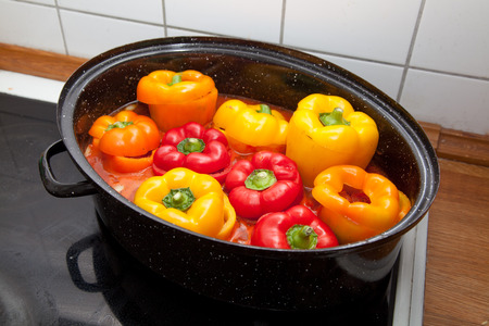 mediteranean: Filled capsicum in casserole with tomato sauce in the kitchen.