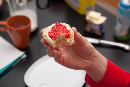 scone: woman holding scone with strawberry marmelade jam at the breakfast table.