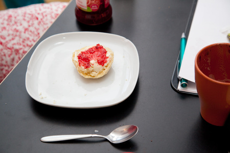 scone: scone with strawberry marmelade jam at the breakfast table.
