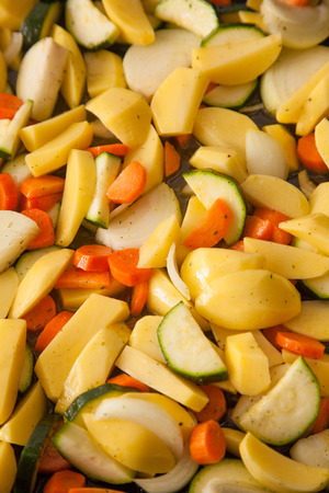vegetable tray: mixed chopped vegetable in a deep baking tray. It is raw vegetable.