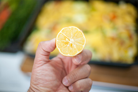 food staple: man holding lemon half  in his hand in the kitchen