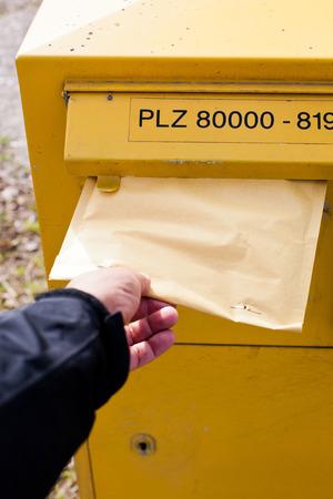 buzon: hombre poniendo un sobre en un buzón.