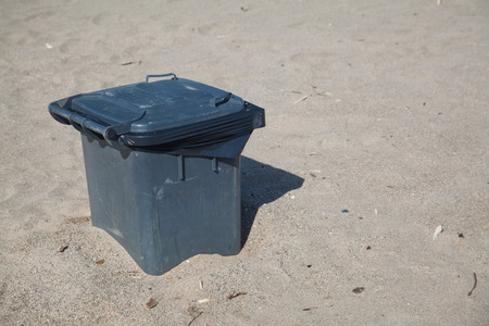 trashcan: Trashcan at a beach in burried in the sand