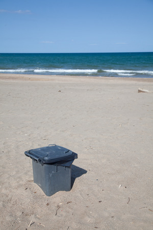burried: Trashcan at a beach in burried in the sand