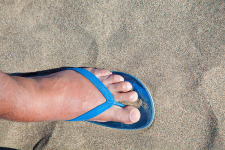 thong: Feet of a man in thong sandals in beach sand