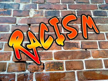 The word racism sprayed on a brickstone wall in orange, yellow, red colors.