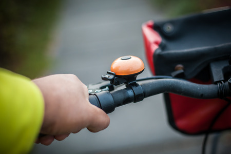 Hand holding a bike handlebar with bike bell. Stockfoto