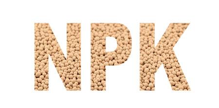 NPK letters made of composite mineral fertilizers on the white  background. N - nitrogen, P - phosphorus, K - potassium (kalium). Selective focus