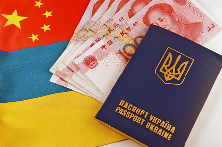 Ukrainian passport and yuans closeup on background of flags Ukraine and China