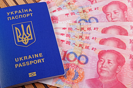 Ukrainian passport and yuans closeup on background of bamboo mat Stock Photo - 119149044